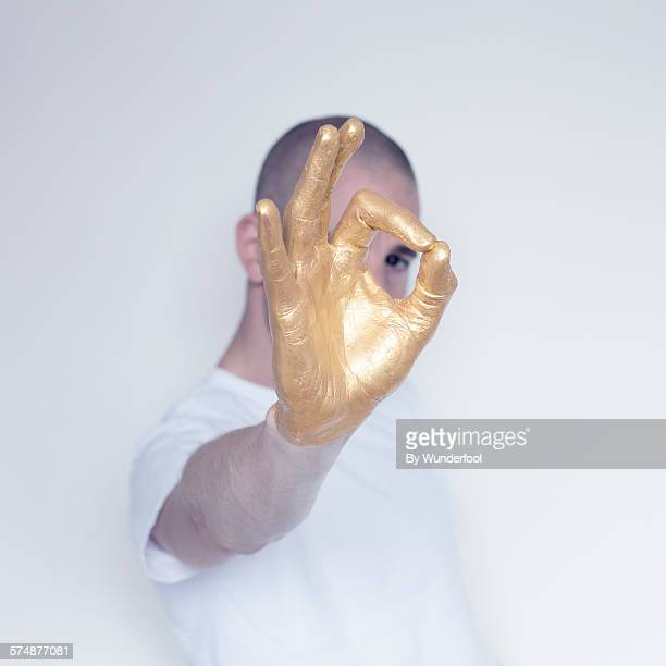 Boy giving the ok sign with a gold hand
