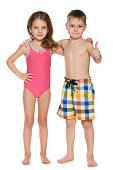 A portrait of two children in swimsuits on the white background