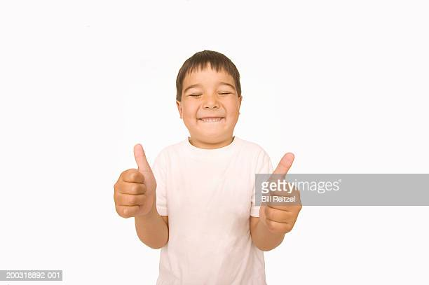 Boy (4-6) giving thumbs up, smiling, eyes closed