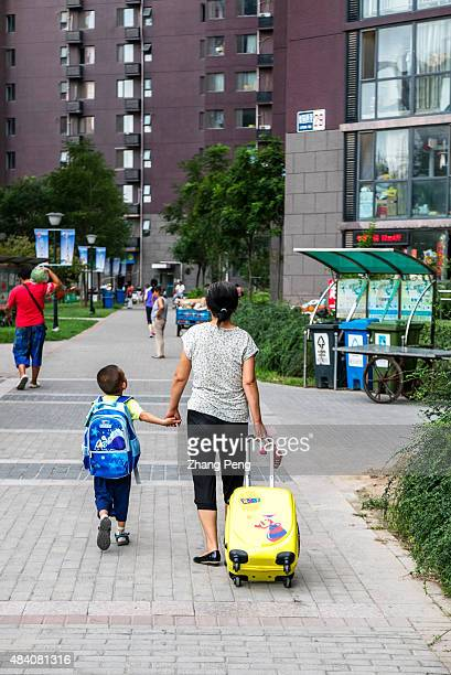A boy goes home with his mother after some summer extracurricular tutoring China is considering whether to allow all couples to have a second child...