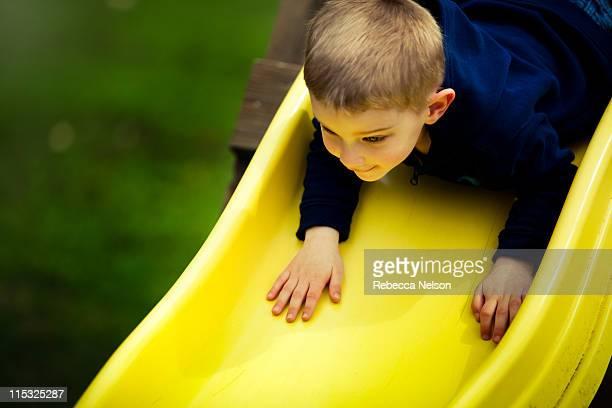 Boy going down yellow slide head first
