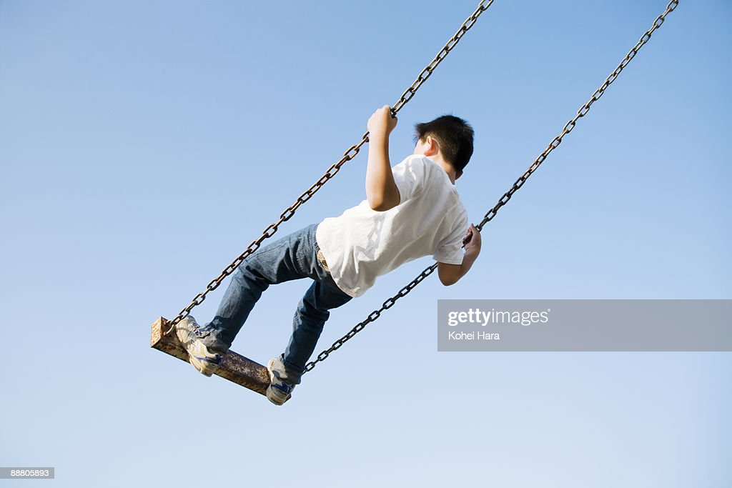 boy going on a swing : Stock Photo