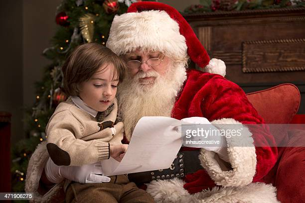Boy going over naughty nice list with Santa