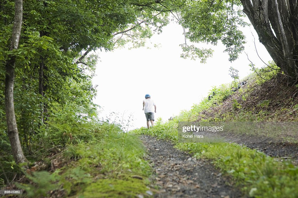 boy going up a slope at mountain : Stock Photo