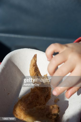 Boy grabs for a fried chicken wing : Stock Photo