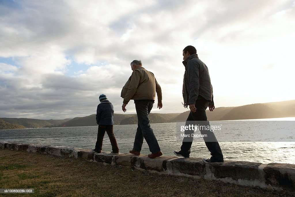 Boy (10-11), grandfather and father walking on wall at edge of lake, rear view : Stock Photo