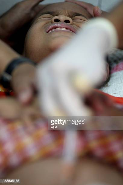 A boy grimaces in pain as he is circumcised with a group of others during a ceremony in Kajang outside Kuala Lumpur on November 20 2011 About 30 boys...