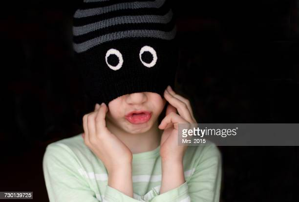 Boy grimacing and pulling a beanie over his eyes