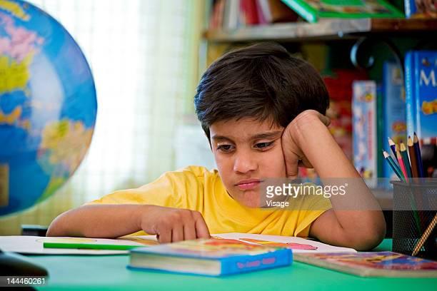 Boy grimacing at his desk