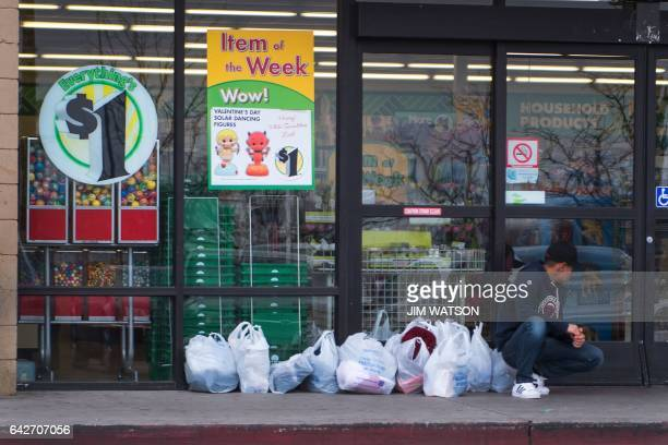A boy guards his family's shopping bags from Walmart as they continue shopping inside a dollar store in Douglas Arizona on February 18 on the...
