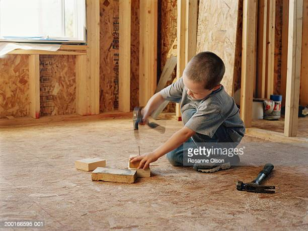 Boy (5-7) hammering nail into wood on construction site, side view