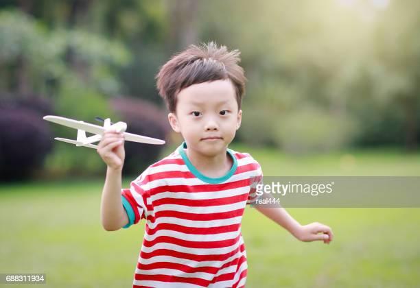 Hand van de jongen met een papieren vliegtuig