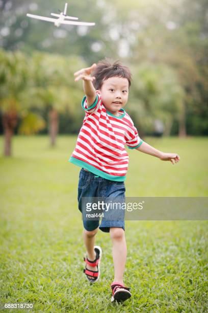 Mano de niño sosteniendo un avión de papel