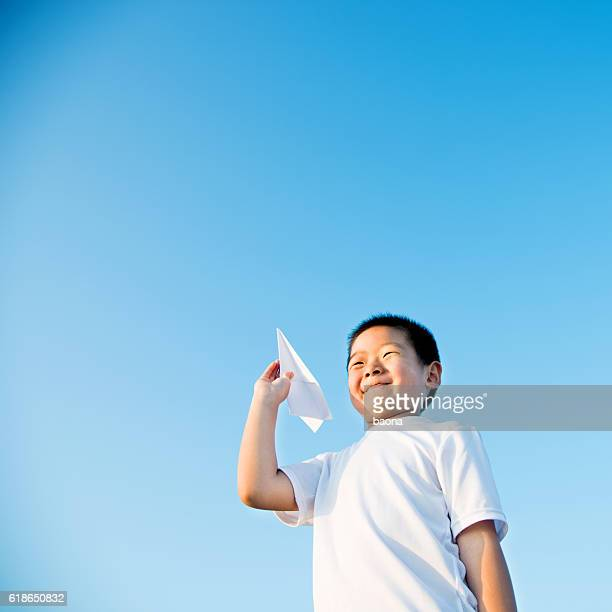 Boy hand holding a paper plane with view of sky