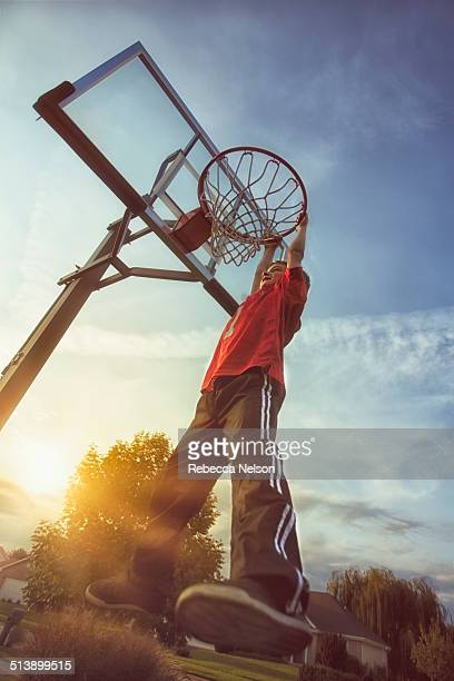 boy hanging from basketball hoop rim