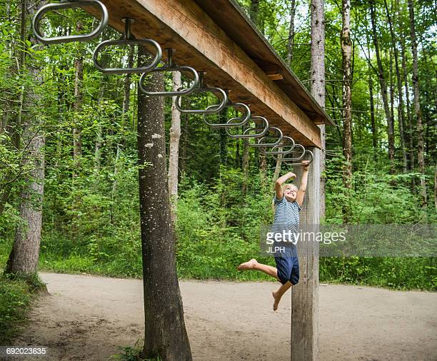 Boy hanging from monkey bars in playground