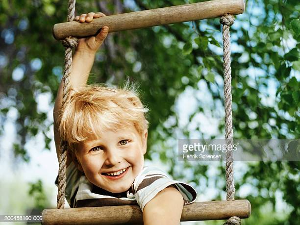 Boy (3-5) hanging from rope ladder, smiling, portrait, close-up