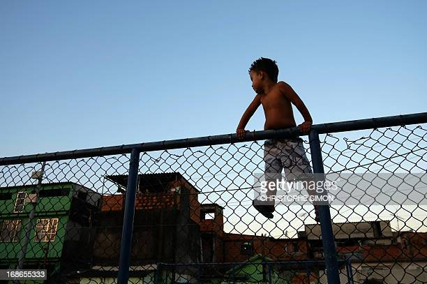 A boy hanging on a fence looks at children playing football in the Cidade de Deus shantytown in Rio de Janeiro Brazil on May 11 2013 AFP...