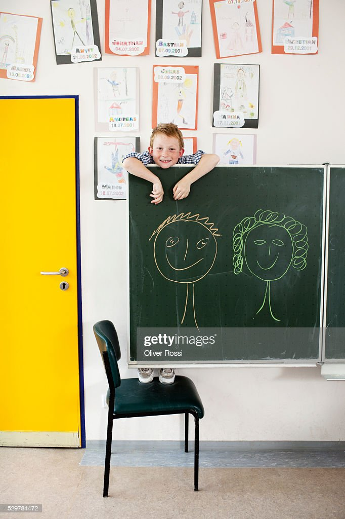 Boy hanging on blackboard : Stock Photo