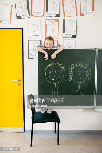 Boy hanging on blackboard : Stock-Foto