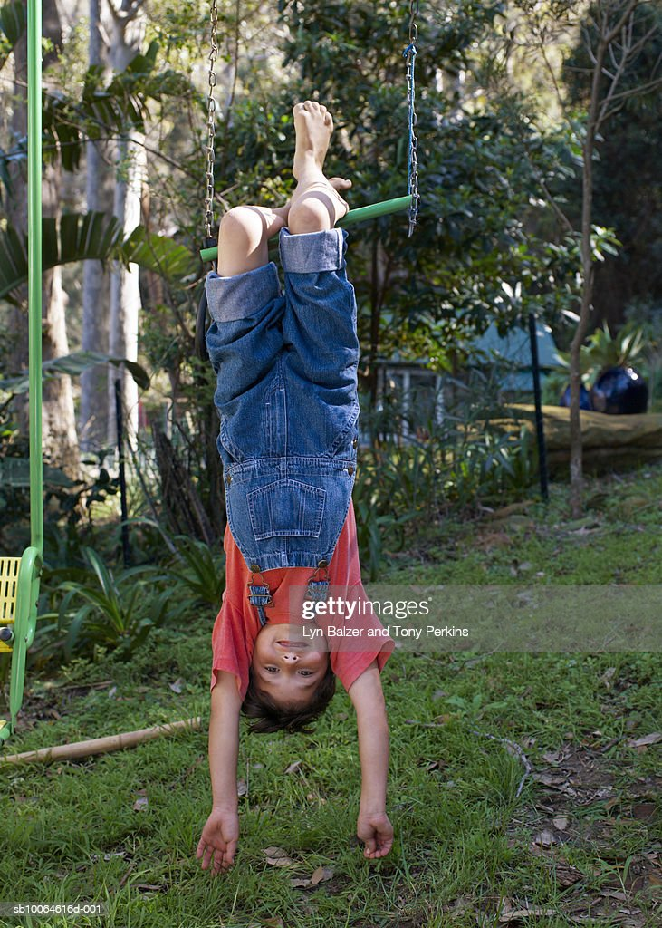 Boy (6-7) hanging upside down from playground swing, portrait : Stock Photo