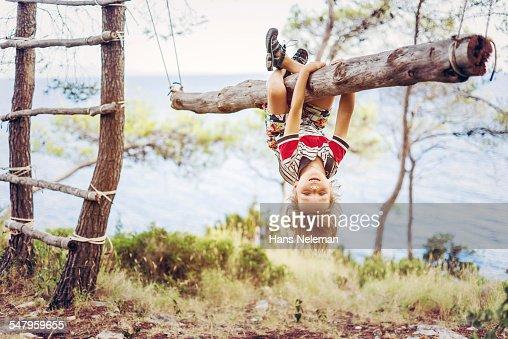 Boy hanging upside down on tree trunk