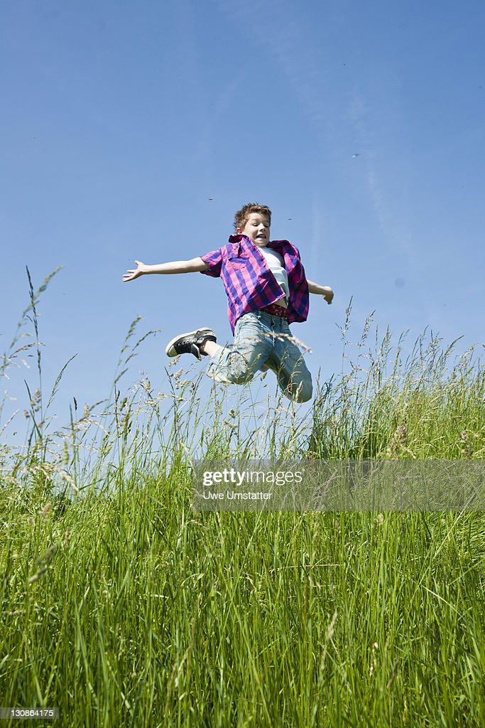 A boy happily jumping in a meadow : Stock Photo