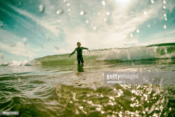 Boy happy and playful in California waves