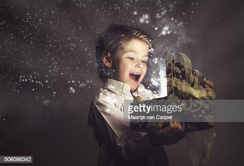 Junge glücklich und Eröffnung Magic Geschenk, Lichtern und Sternen