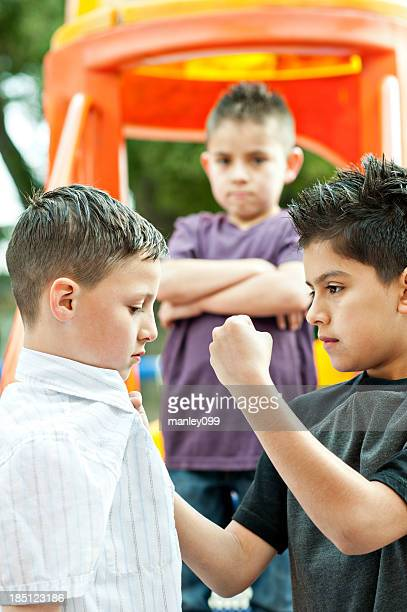 boy harrassed by two bullies