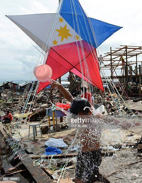 A boy has a bath in front of a giant lantern erected by residents and survivors of Super Typhoon Haiyan amongst the debris in the coastal area of...