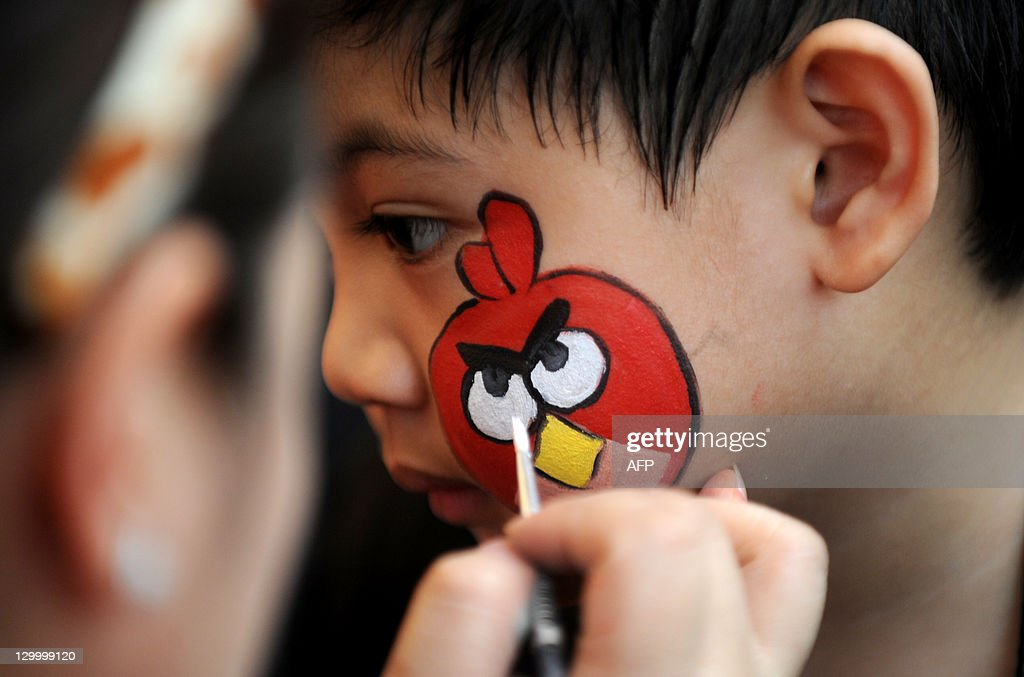 A boy has a character from the popular computer game 'Angry Birds' painted on his face during the Philippine Animal Welfare Society's (PAWS) annual Halloween fund raising event entitled 'Scaredy Cats and Dogs: Year 8' at the Eastwood Central Plaza in Manila on October 23, 2011.