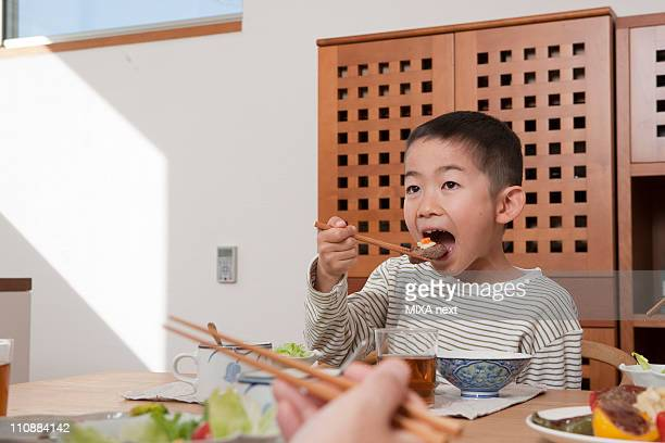 Boy Having a Meal by Chopsticks