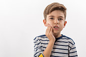 Boy having a toothache holding his face with his hand. white background