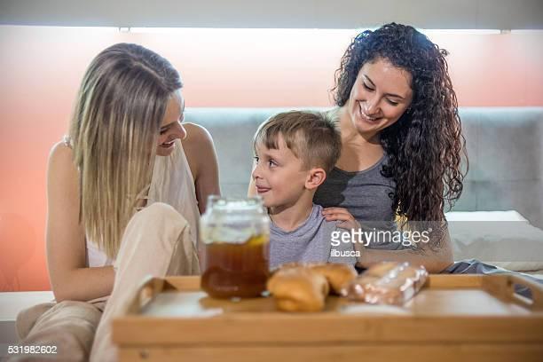 Garçon prenant le petit déjeuner au lit grâce à ses deux sœurs mamans