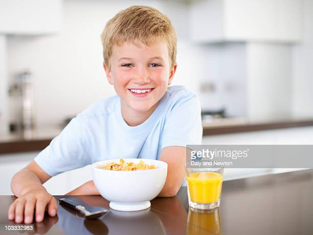 Boy having breakfast of cereal and juice