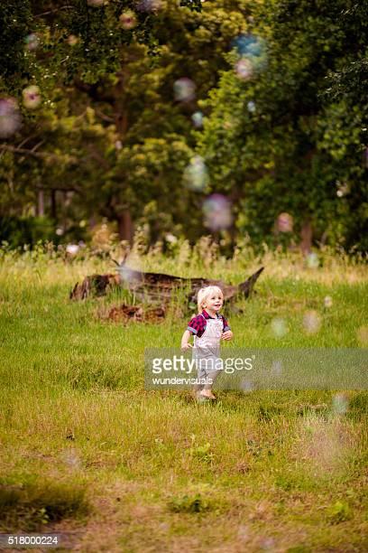 Garçon s'amuser courir après bulles volant dans le parc