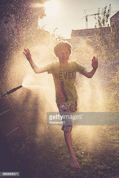 Boy having fun with splashing water in the garden