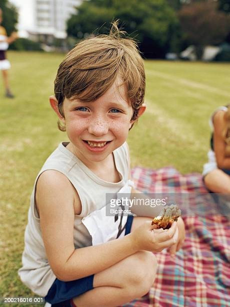 Boy (4-6) having picnic at school sports day, smiling, portrait