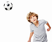 Little boy heads a soccer ball. Horizontal shot. Isolated on white.