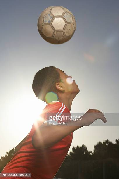 Boy (12-13) heading football, lens flare