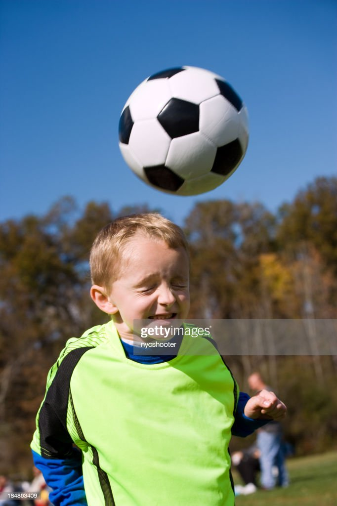 boy heading soccer ball : Stock Photo