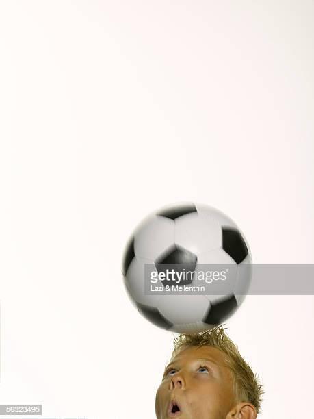 Boy heading soccer ball (blurred motion)