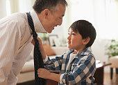 Boy helping father tie his tie
