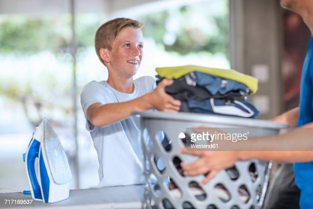 Boy helping father with chores carrying laundry basket