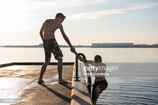 Boy helping friend up from water on pier : Stock Photo