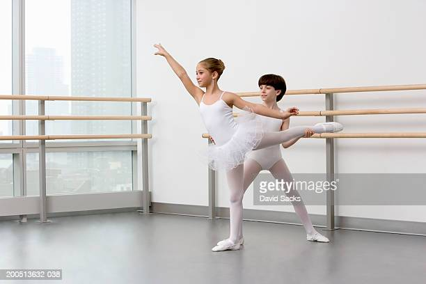 Boy (12-14) helping girl (8-10) perform arabesque in ballet class