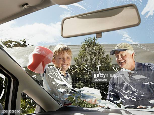Boy (7-9) helping grandfather clean car windscreen with soapy sponge