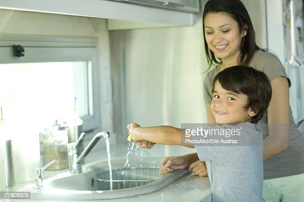 Boy helping mother wash dishes, looking over shoulder at camera