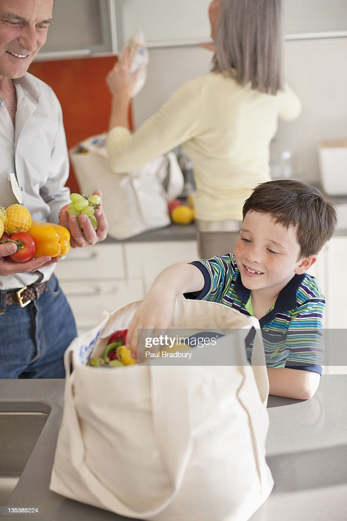 Boy helping to unload groceries from reusable bag